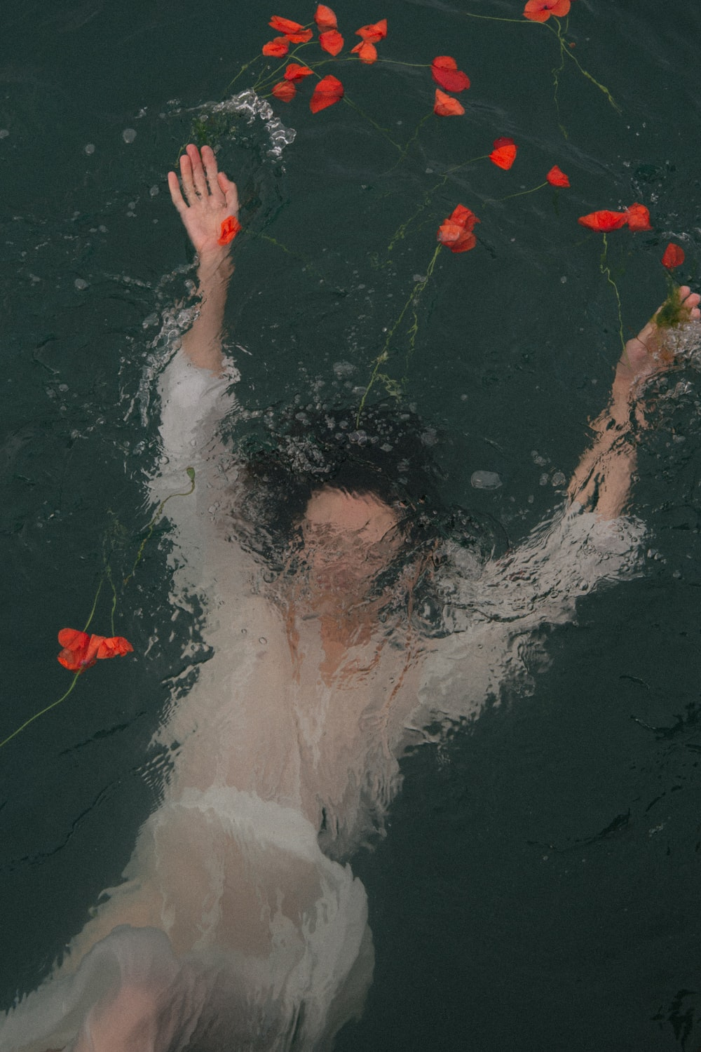 woman in water with red petals