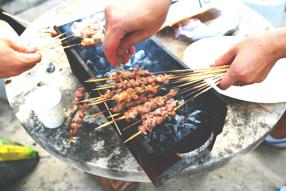 person holding fork and knife slicing meat on black and gray grill