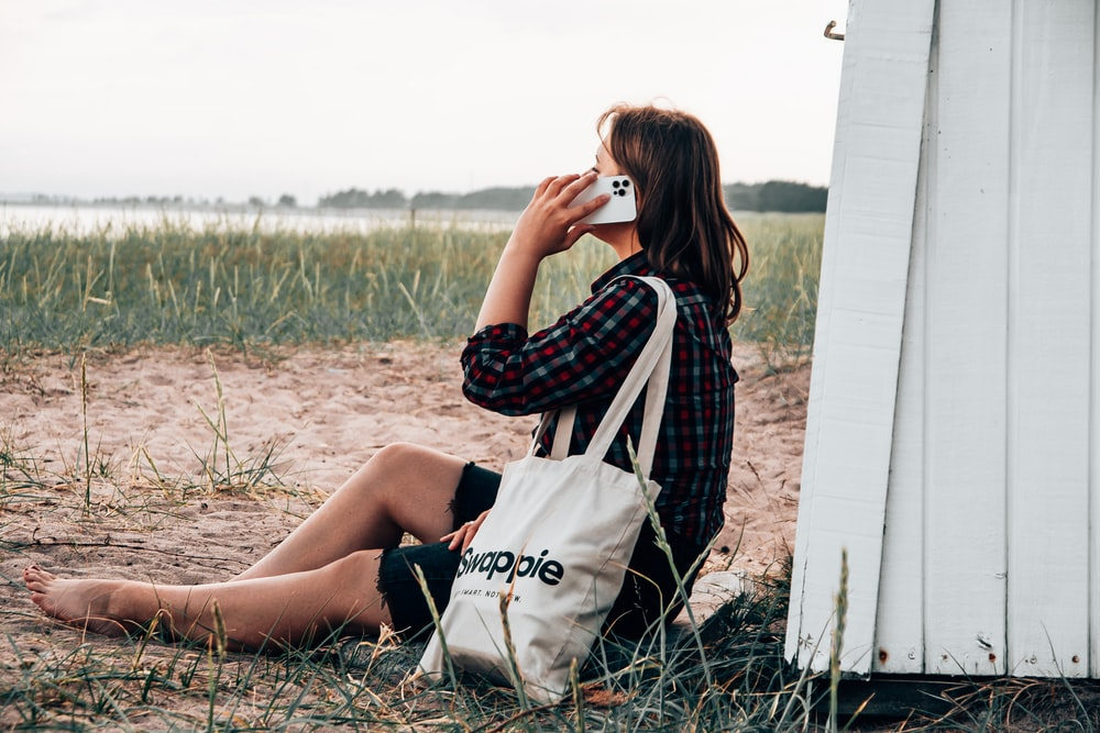 woman in black and white checkered long sleeve shirt sitting on brown grass field during daytime