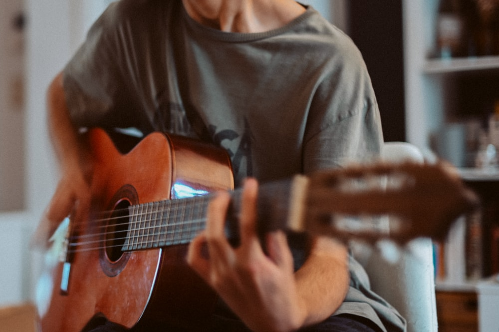 man in gray crew neck shirt playing brown acoustic guitar