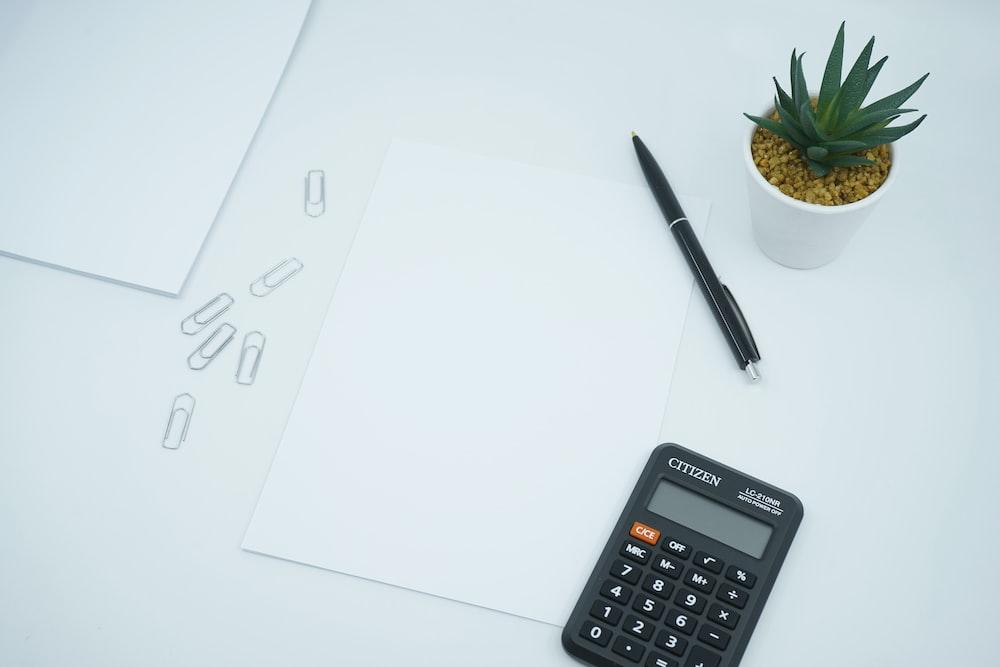 black calculator beside black pen on white printer paper