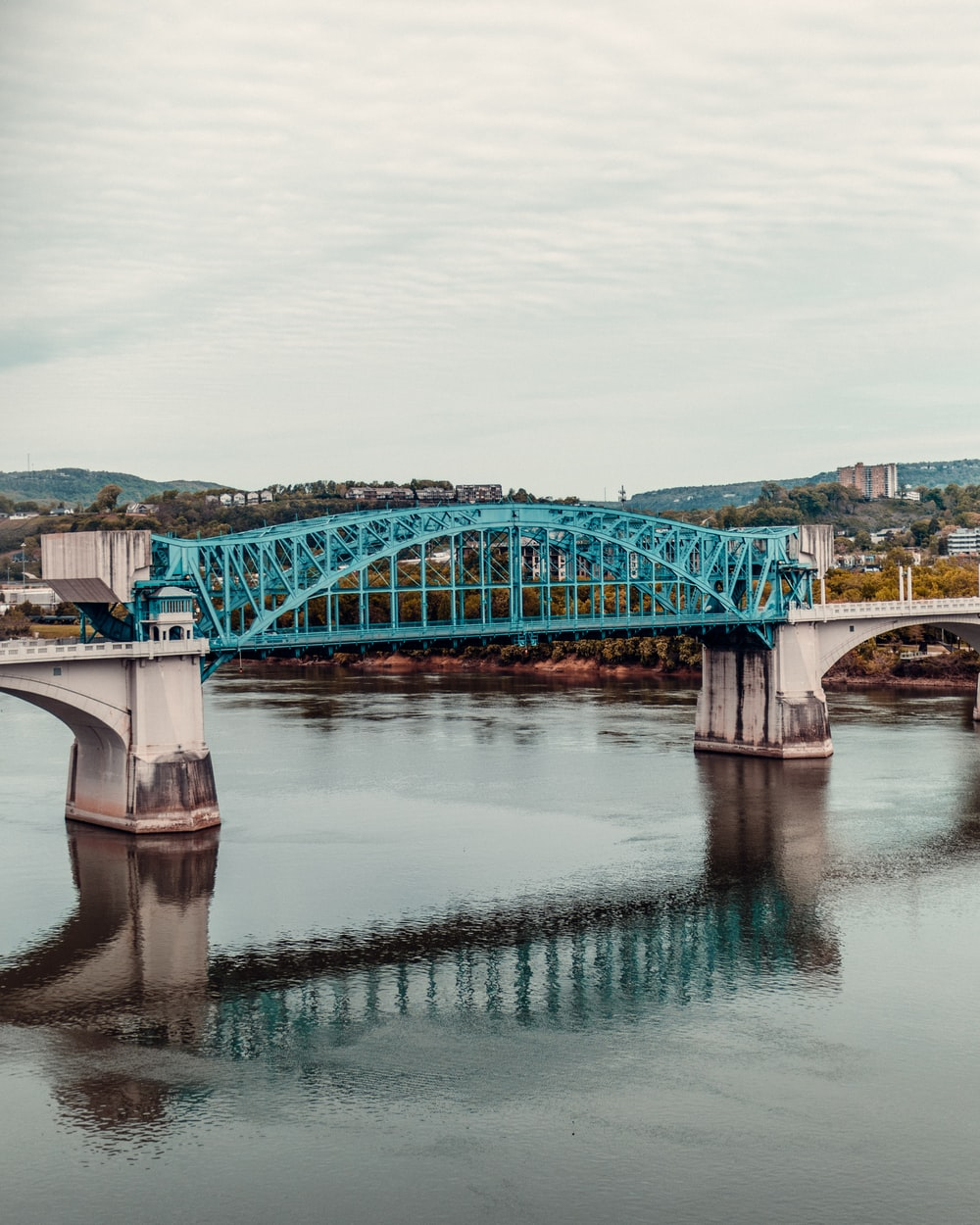 blue and white bridge over river under white clouds