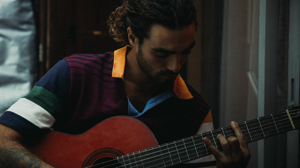 man in purple and black collared shirt playing guitar