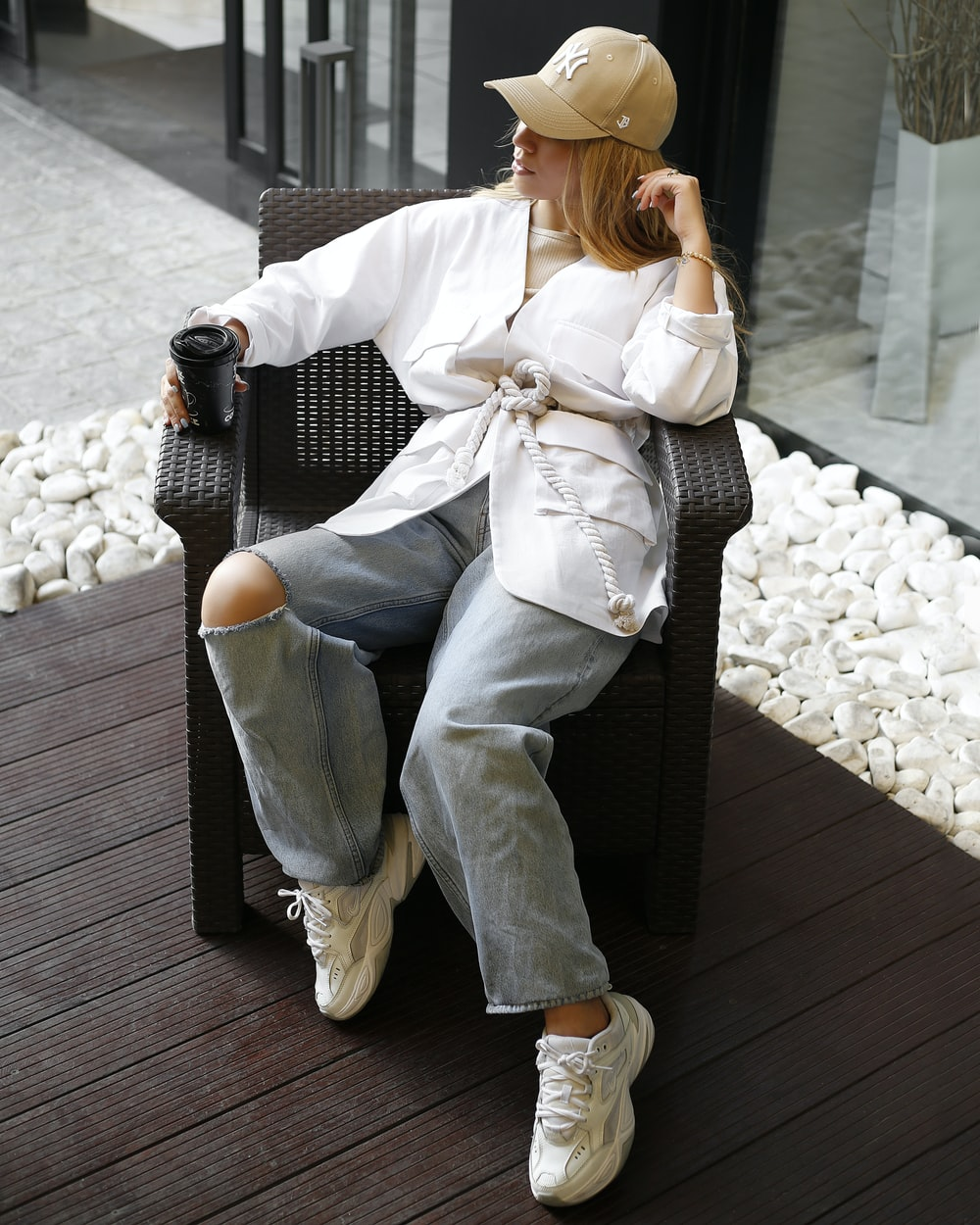 woman in white long sleeve shirt and blue denim jeans sitting on black wooden bench during