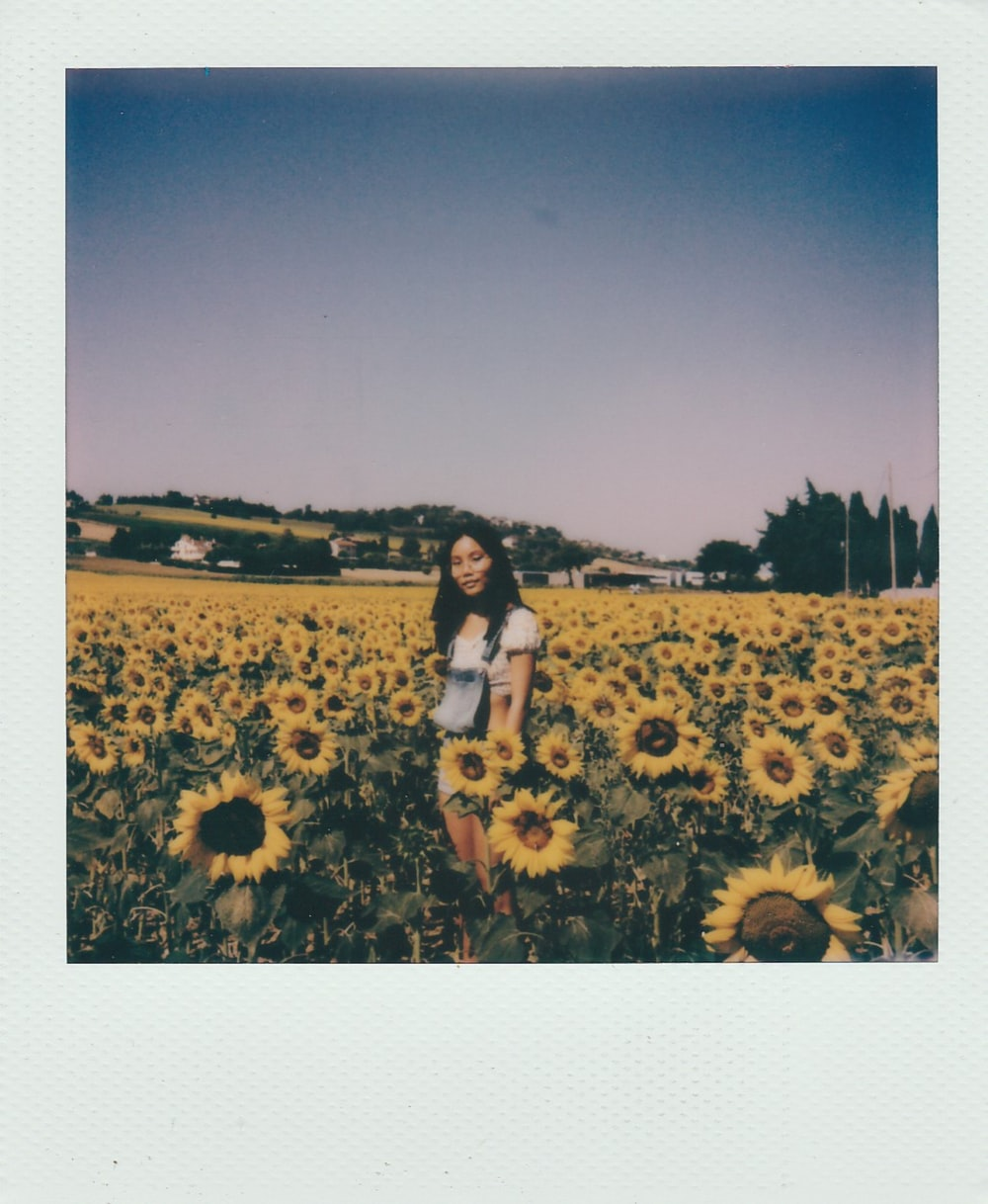 woman in black tank top and white shorts standing on sunflower field during daytime