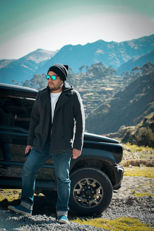 man in black jacket and blue denim jeans standing beside black car
