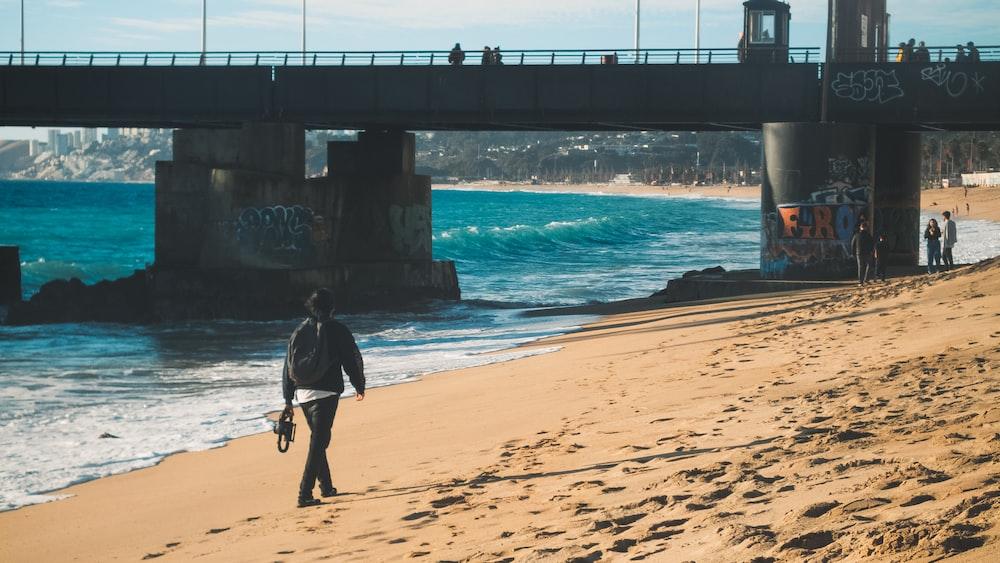 man in black jacket walking on beach during daytime