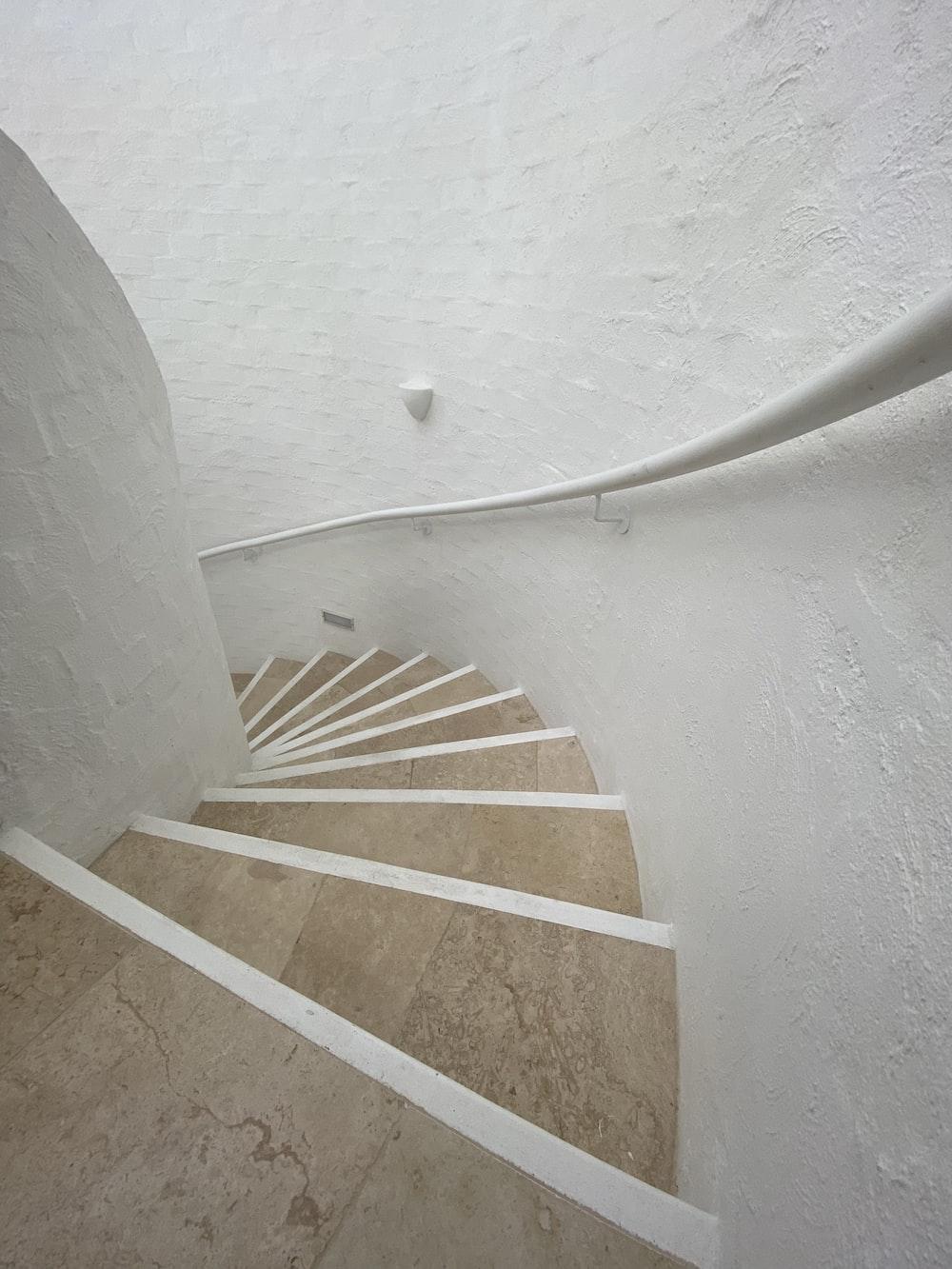 white concrete spiral staircase with white concrete wall
