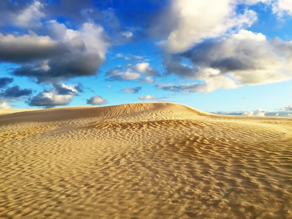 brown sand under blue sky and white clouds during daytime