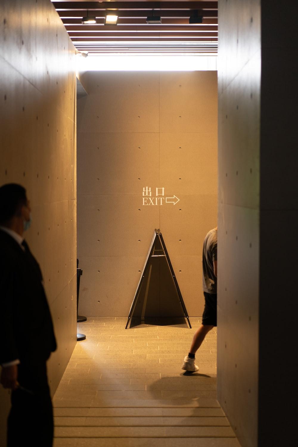 man in black coat walking on hallway