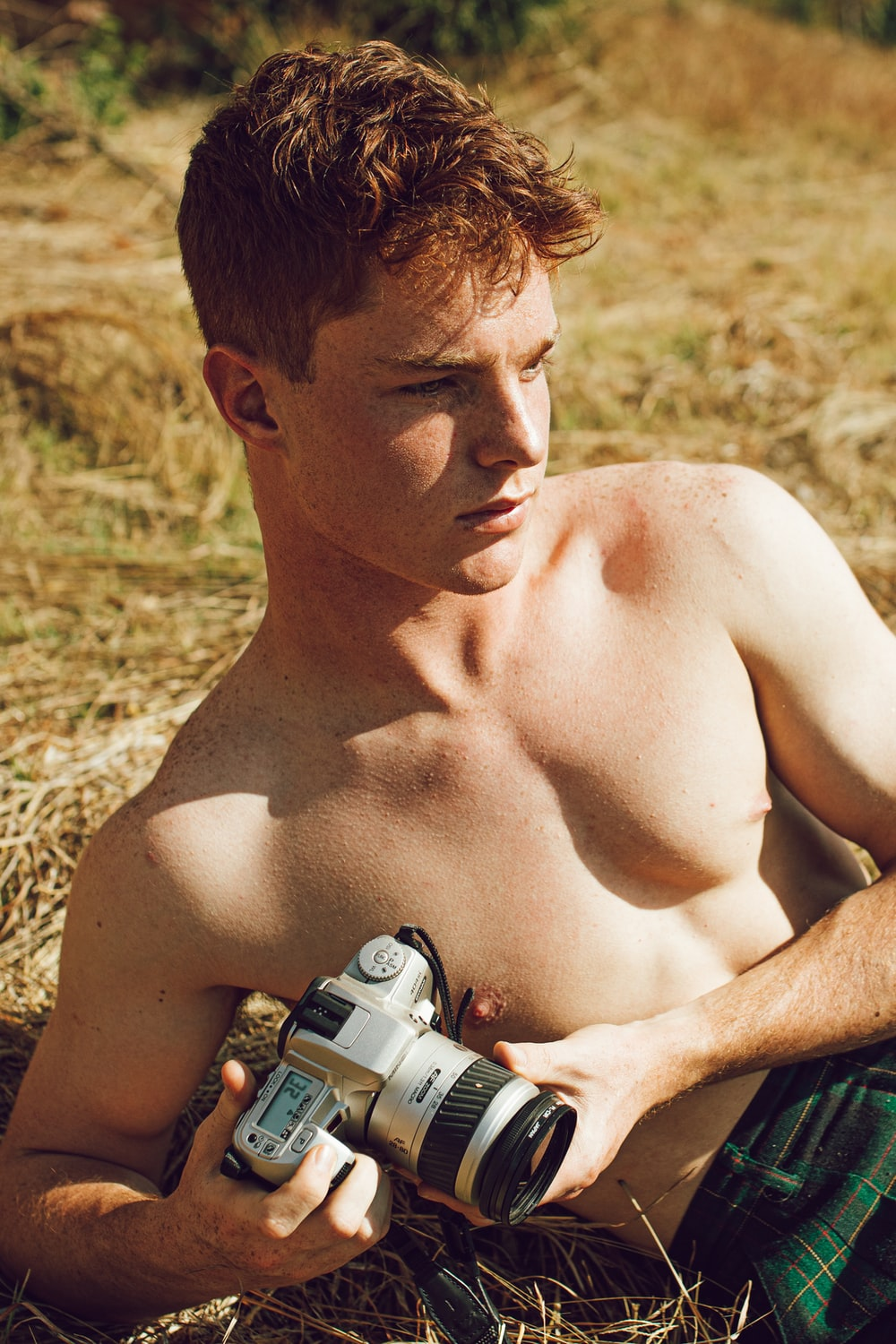 topless man holding black and gray dslr camera