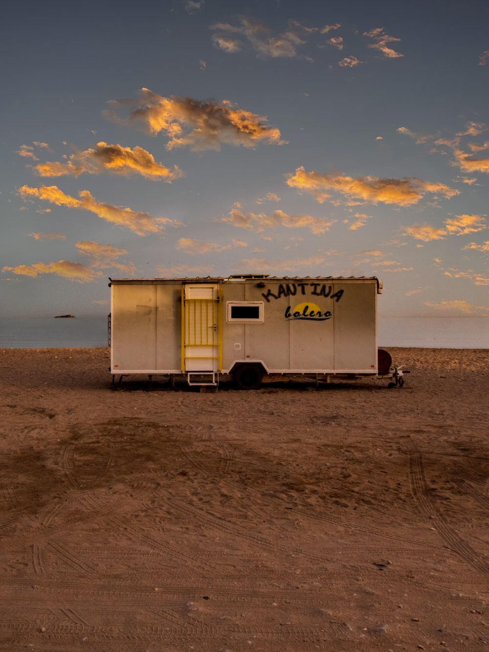 white and red camper trailer on beach during sunset
