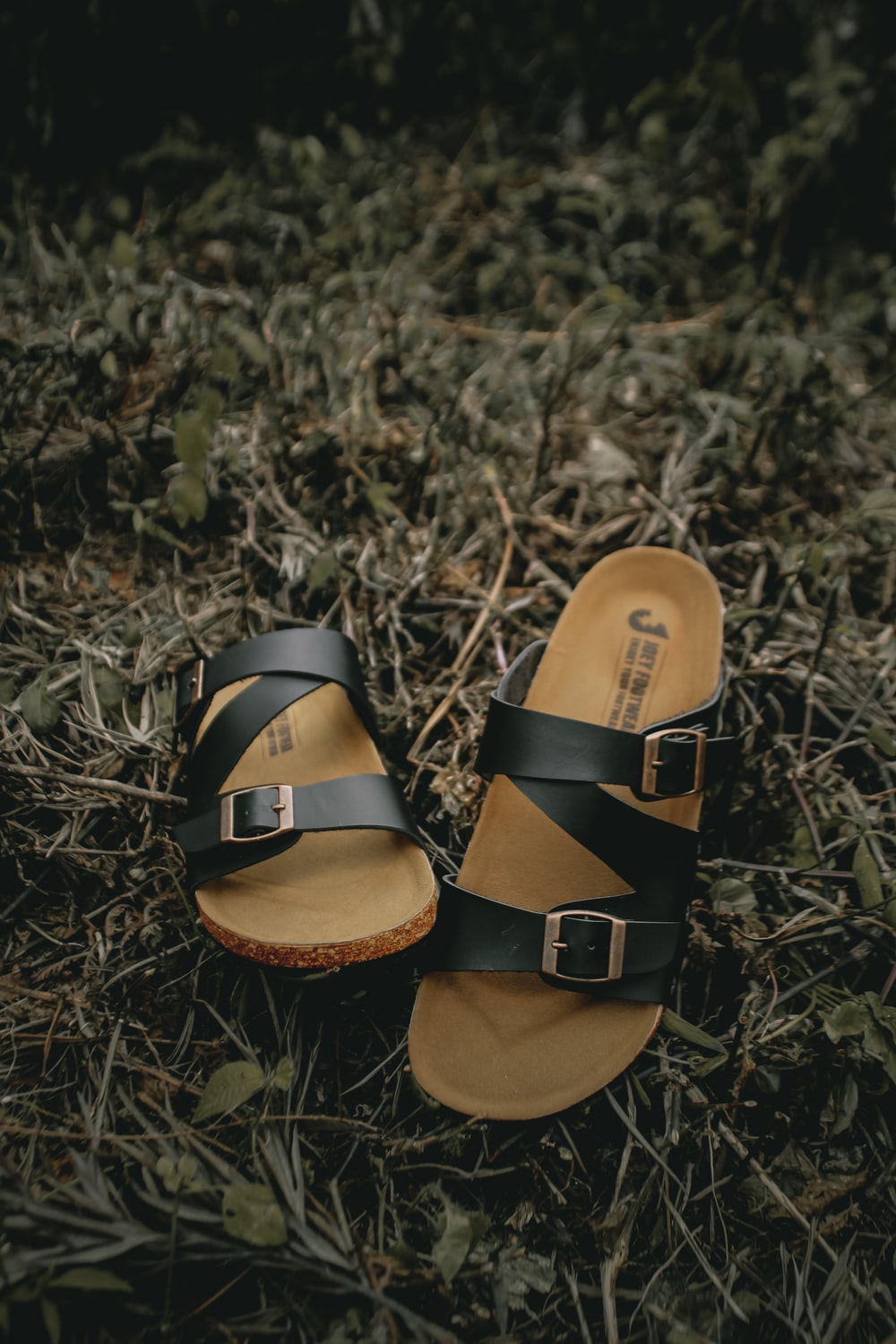 brown and black leather sandals on green grass