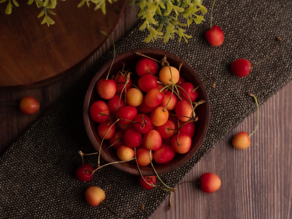 red and green round fruits on brown round bowl