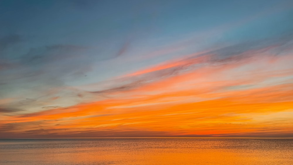 body of water under orange and blue sky