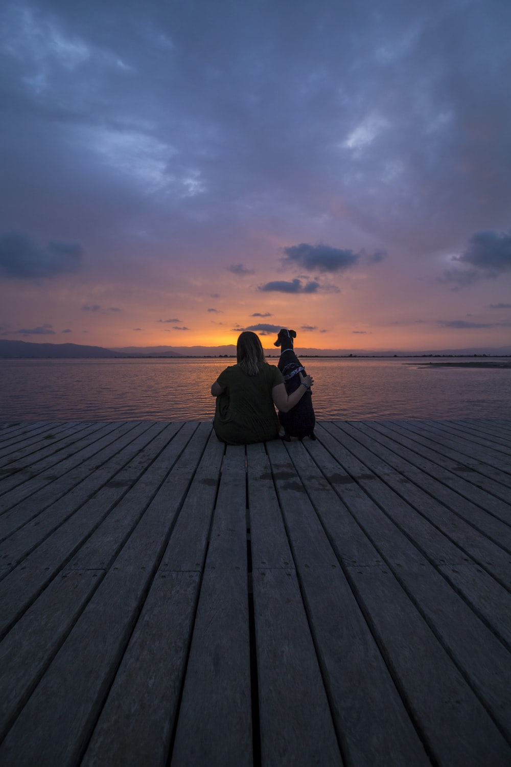 woman in black jacket sitting on wooden dock during sunset