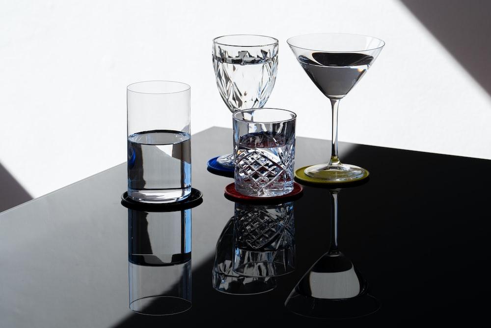 clear wine glass beside clear glass bottle