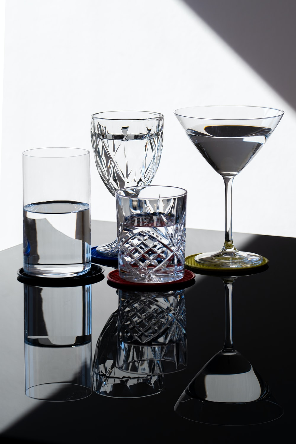 clear wine glass beside clear drinking glass