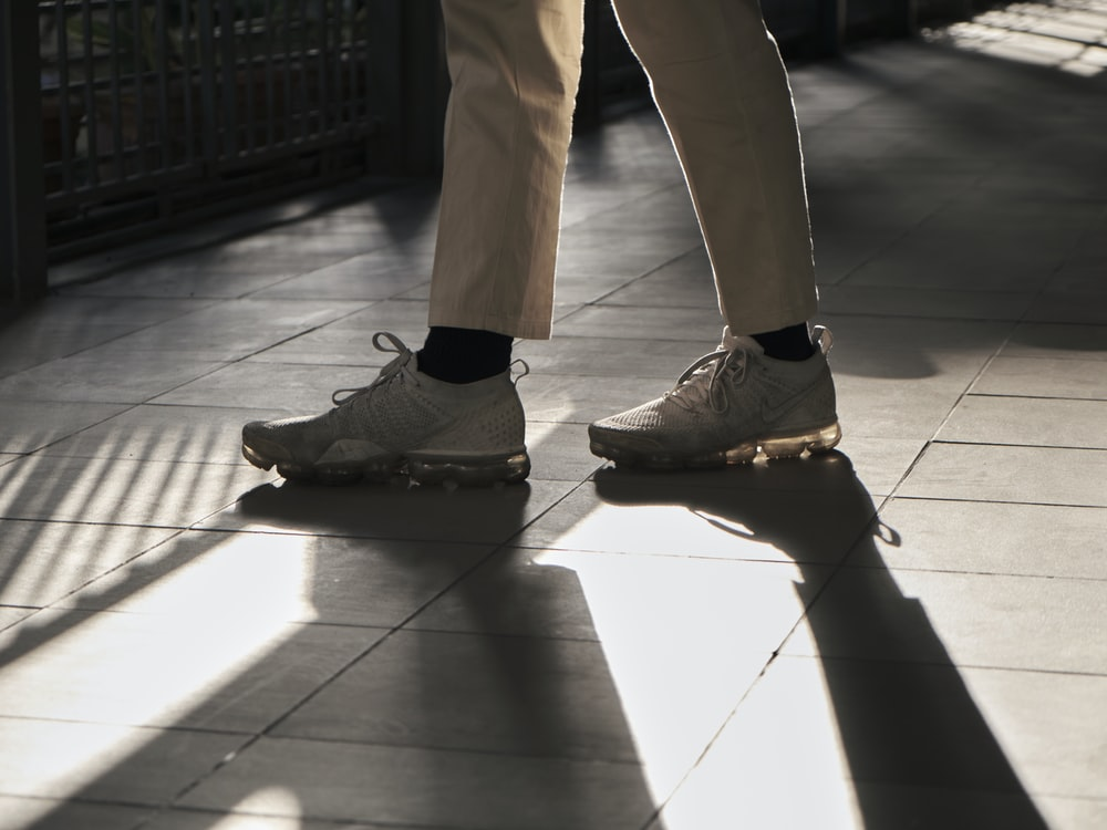 person in brown pants and black nike sneakers