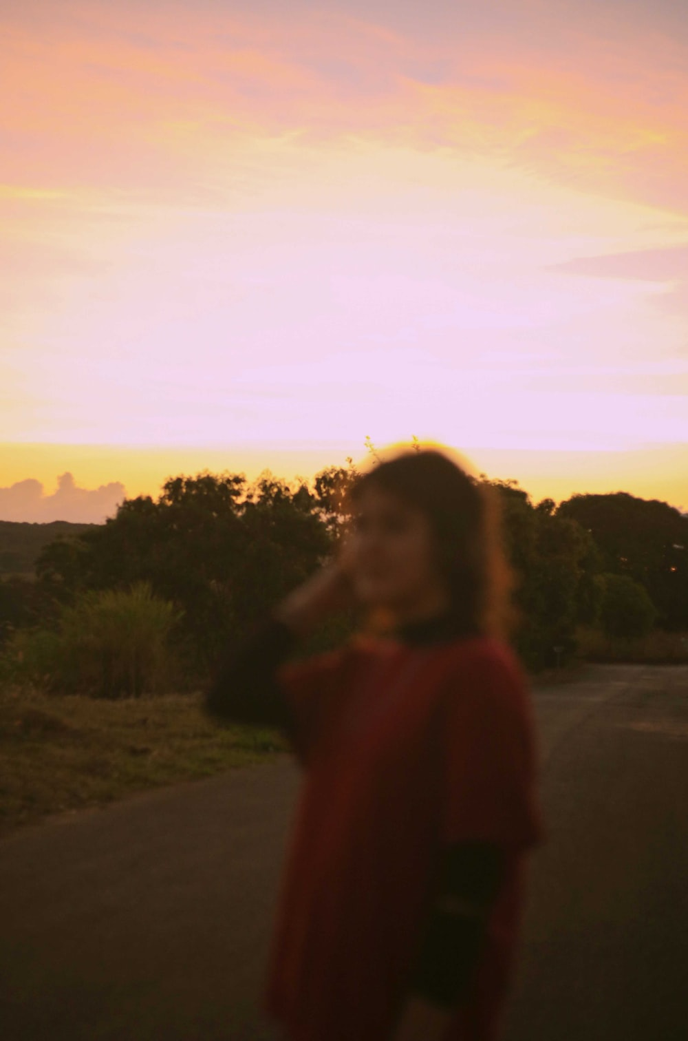 woman in red shirt standing on road during sunset