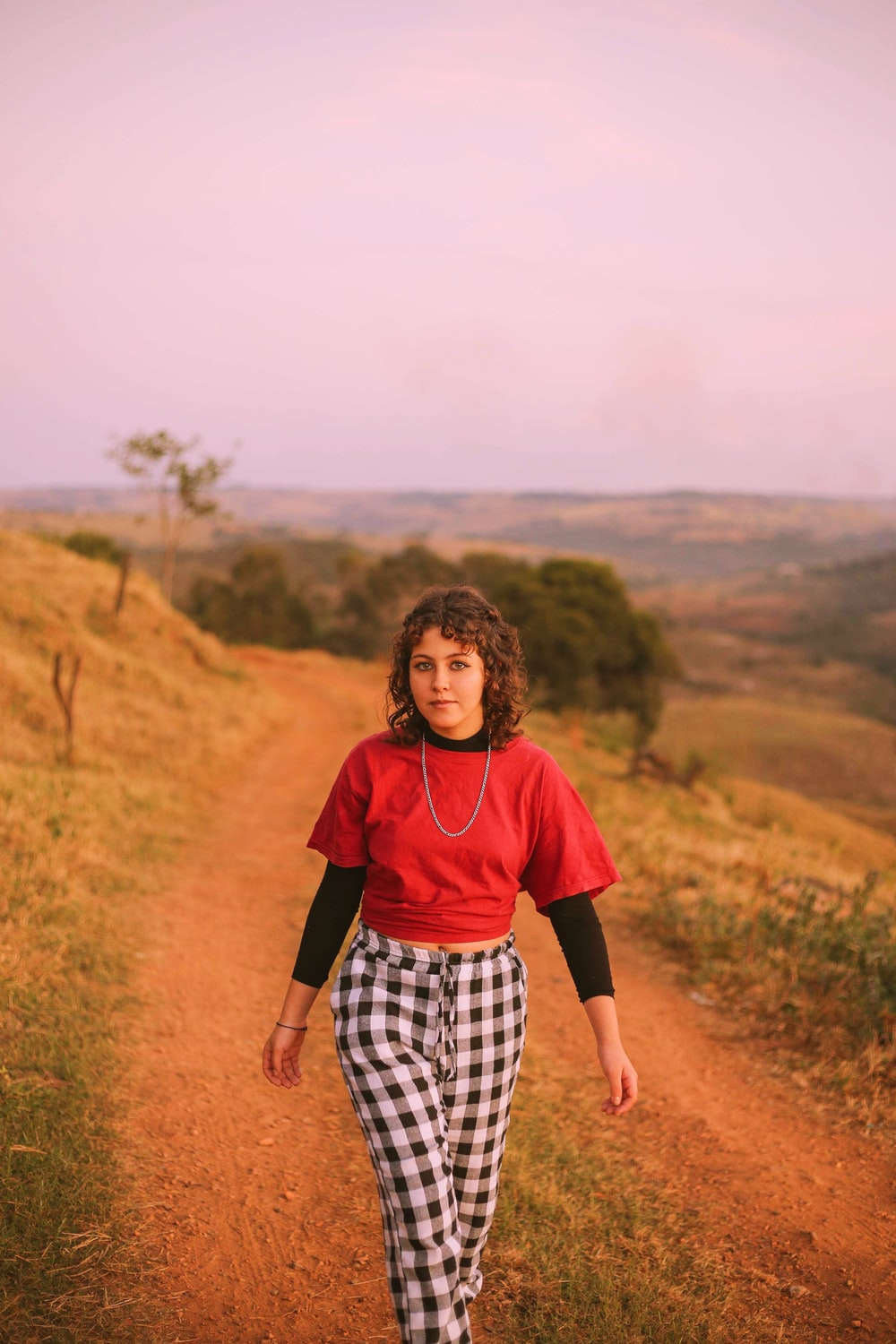 woman in red shirt and black and white checkered pants walking on brown field during daytime