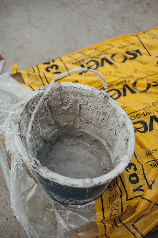 gray metal bucket on yellow paper