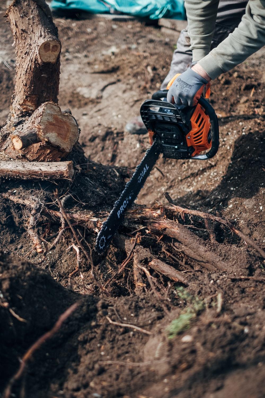 orange and black power tool on brown wood log