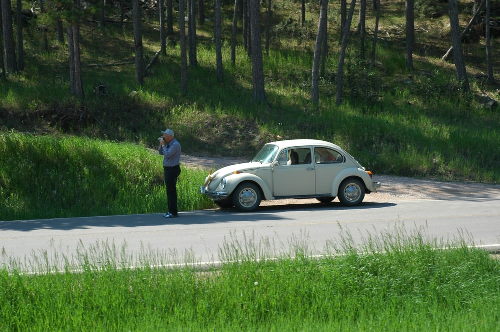 man in black shirt and blue denim jeans standing beside white sedan on road during daytime