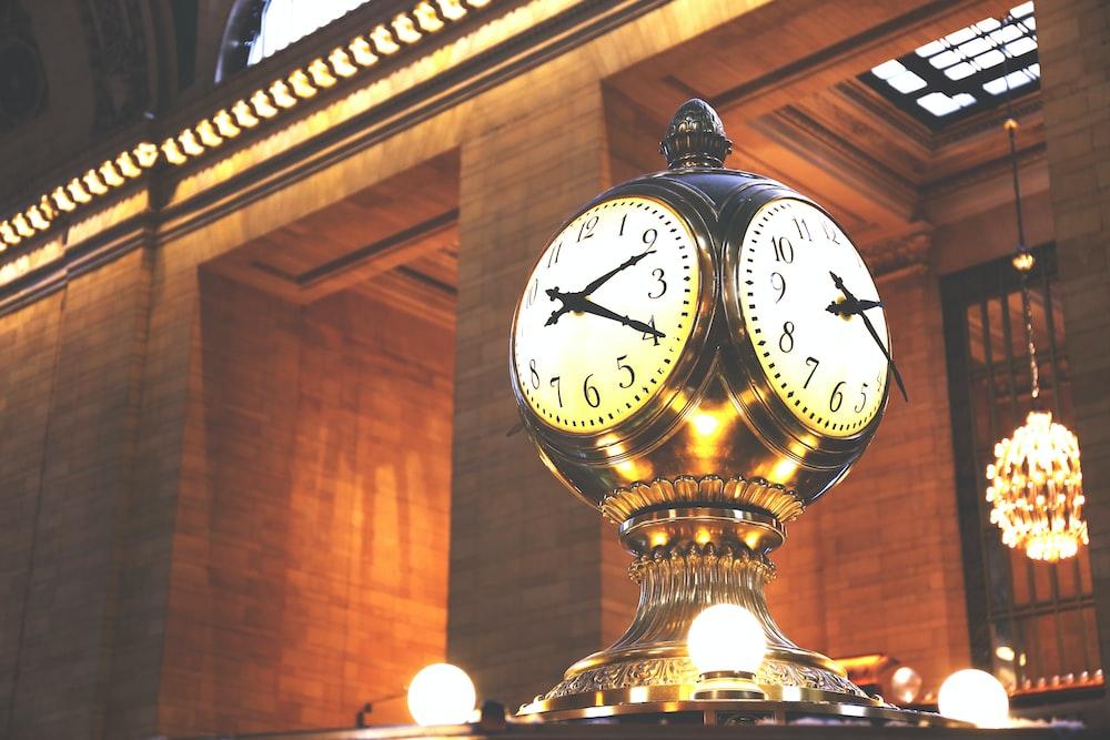 gold and white analog clock at 10 00