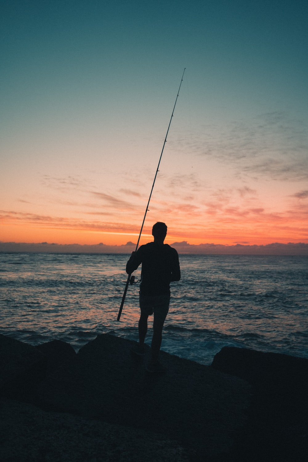 silhouette of man fishing on sea during sunset