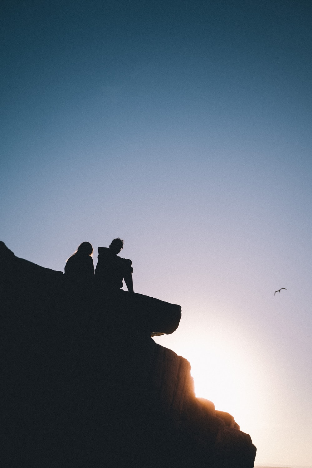 silhouette of 2 men sitting on rock formation during sunset