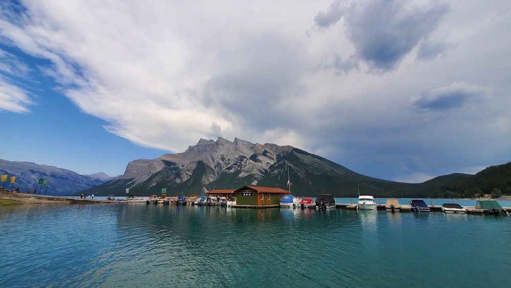 brown wooden house on body of water near mountain under white clouds during daytime