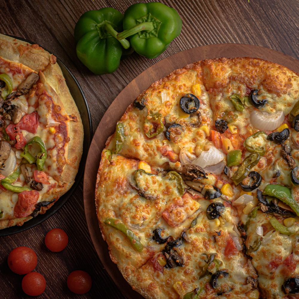 pizza with green bell pepper and cheese on brown wooden table