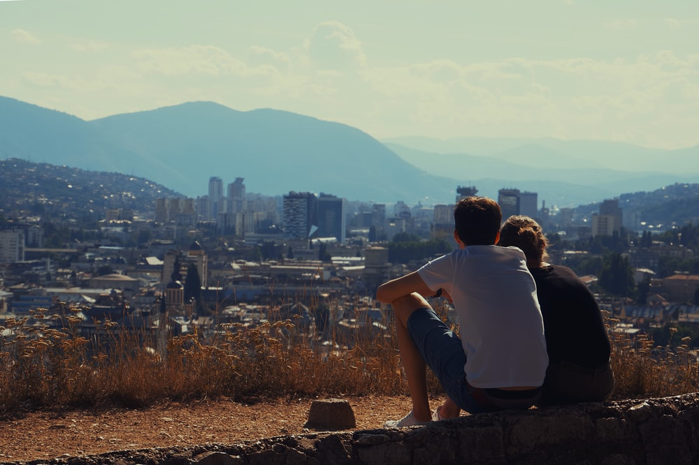 man and woman sitting on brown concrete fence during daytime