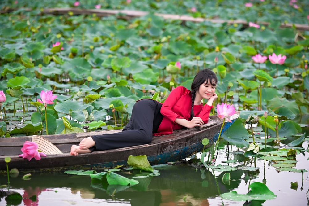 woman in red long sleeve shirt sitting on brown boat during daytime