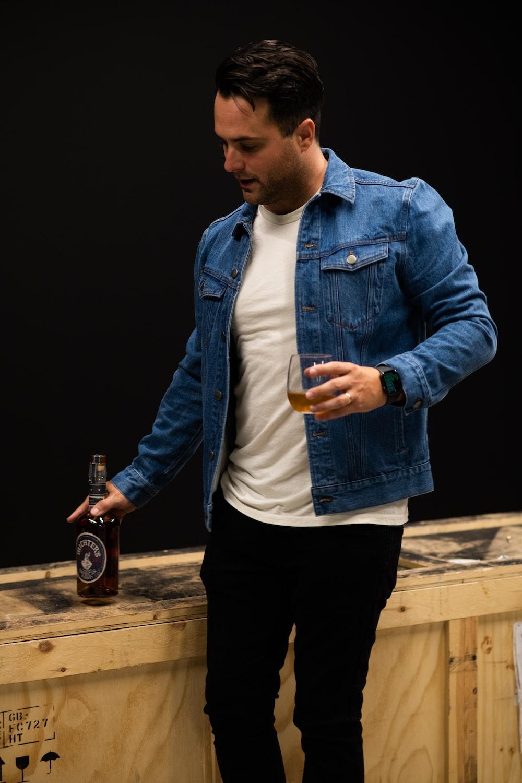 man in blue denim jacket holding bottle