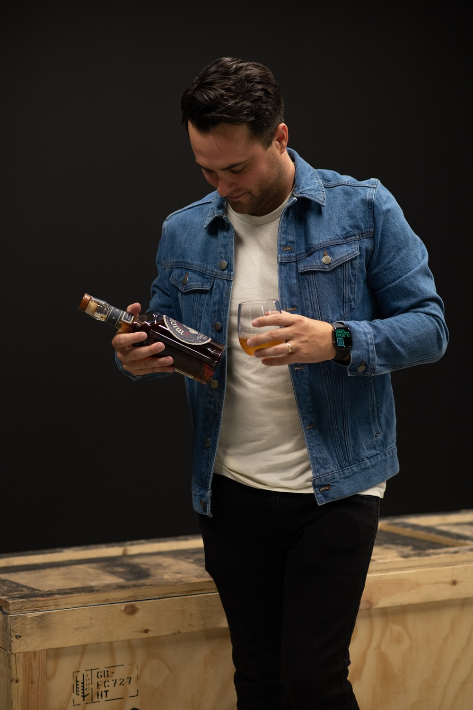 man in blue denim jacket holding smartphone