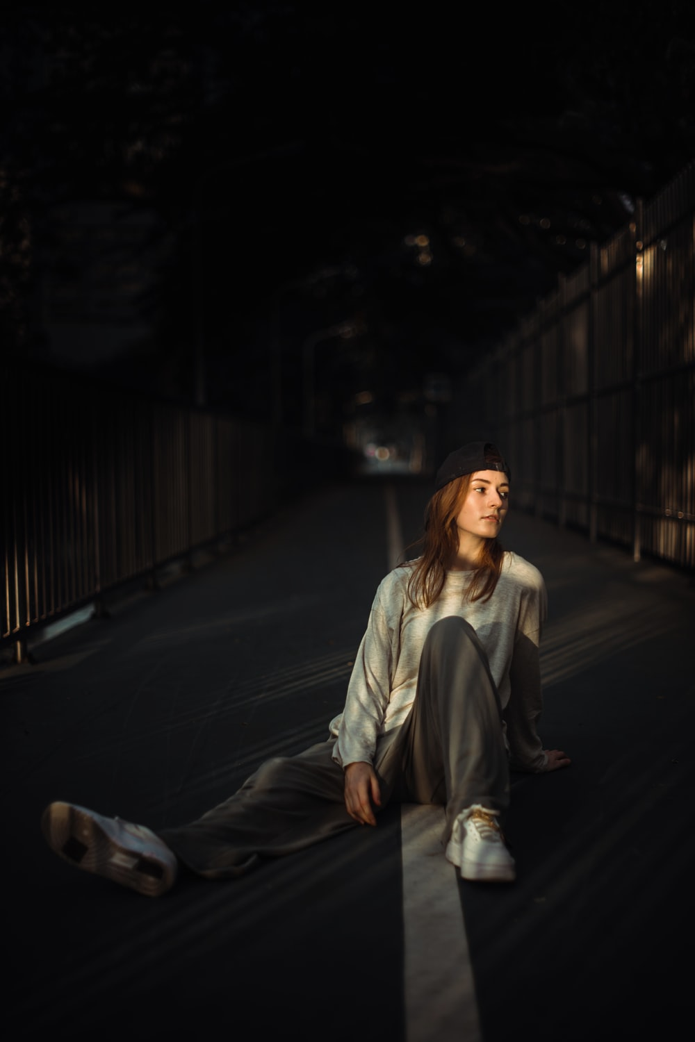 woman in gray coat sitting on the sidewalk during night time