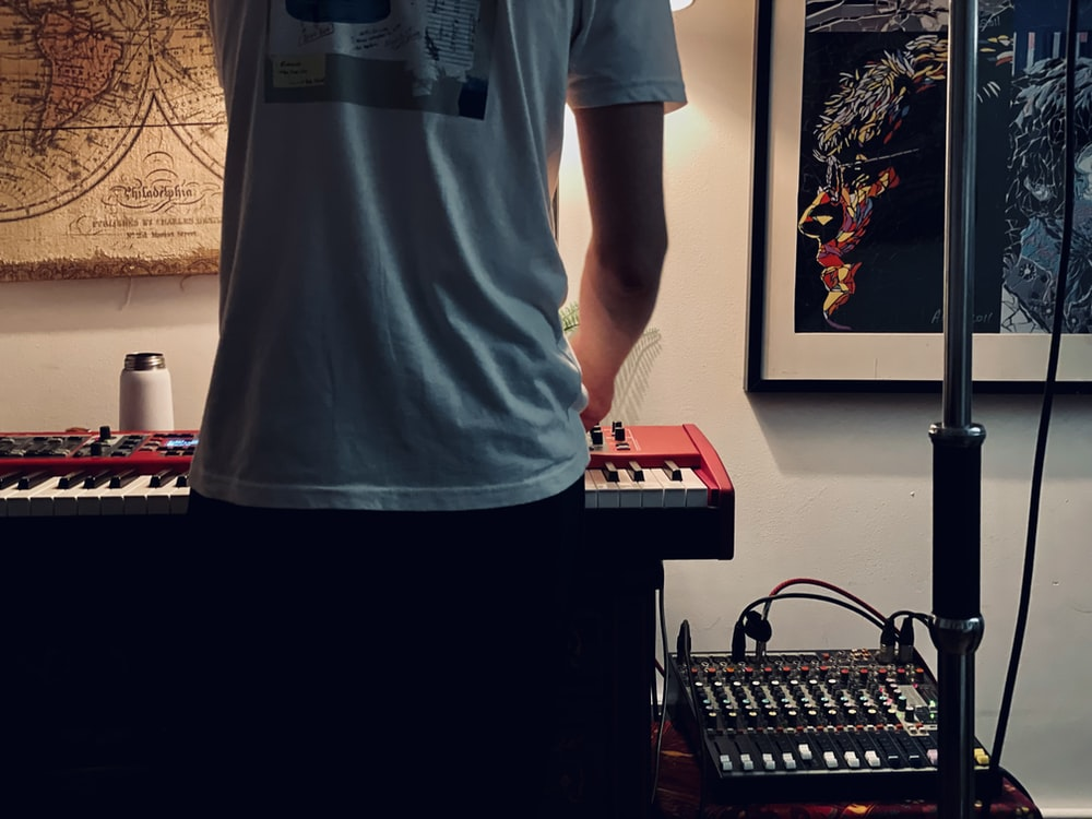 man in white crew neck t-shirt standing near black computer keyboard