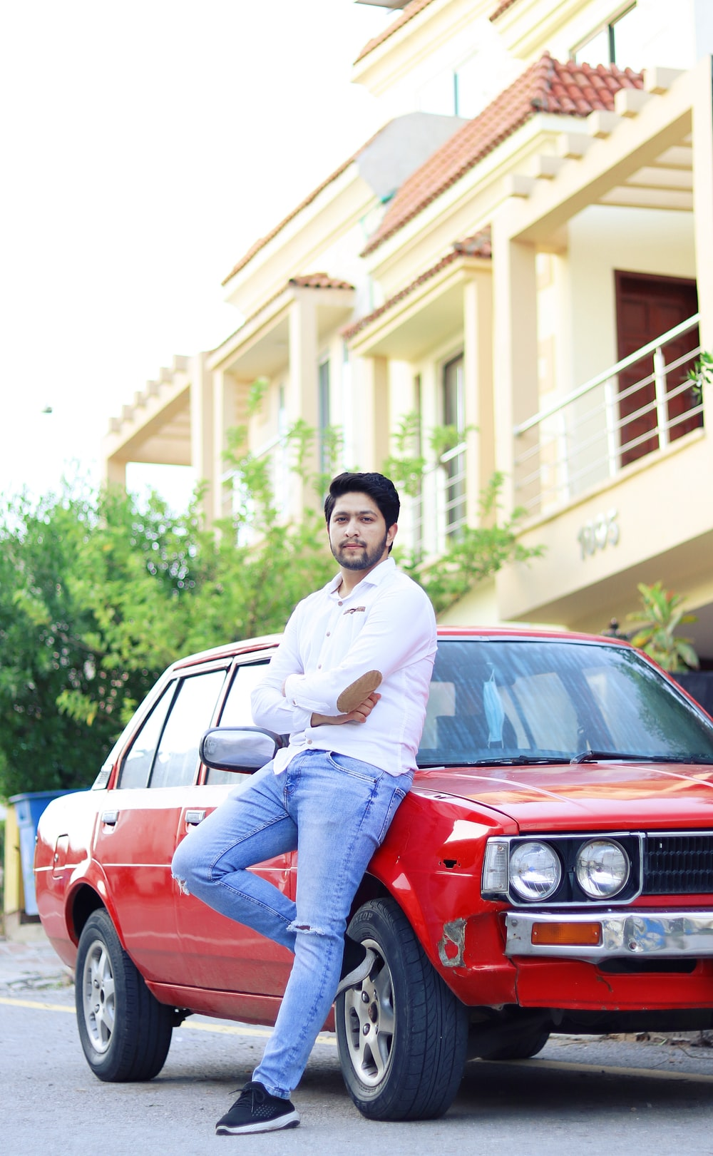 man in white dress shirt and blue denim jeans sitting on red car