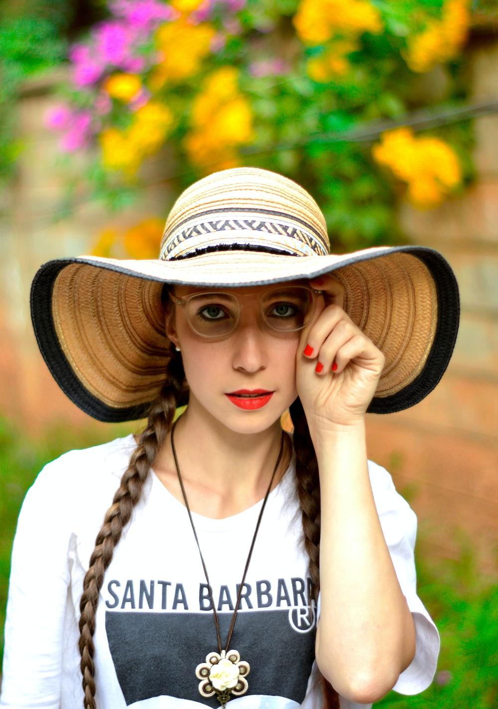woman in white shirt wearing brown straw hat