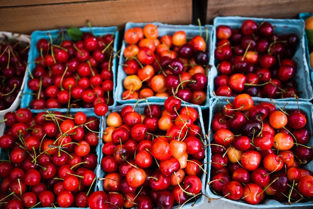 red cherries on brown wooden crate