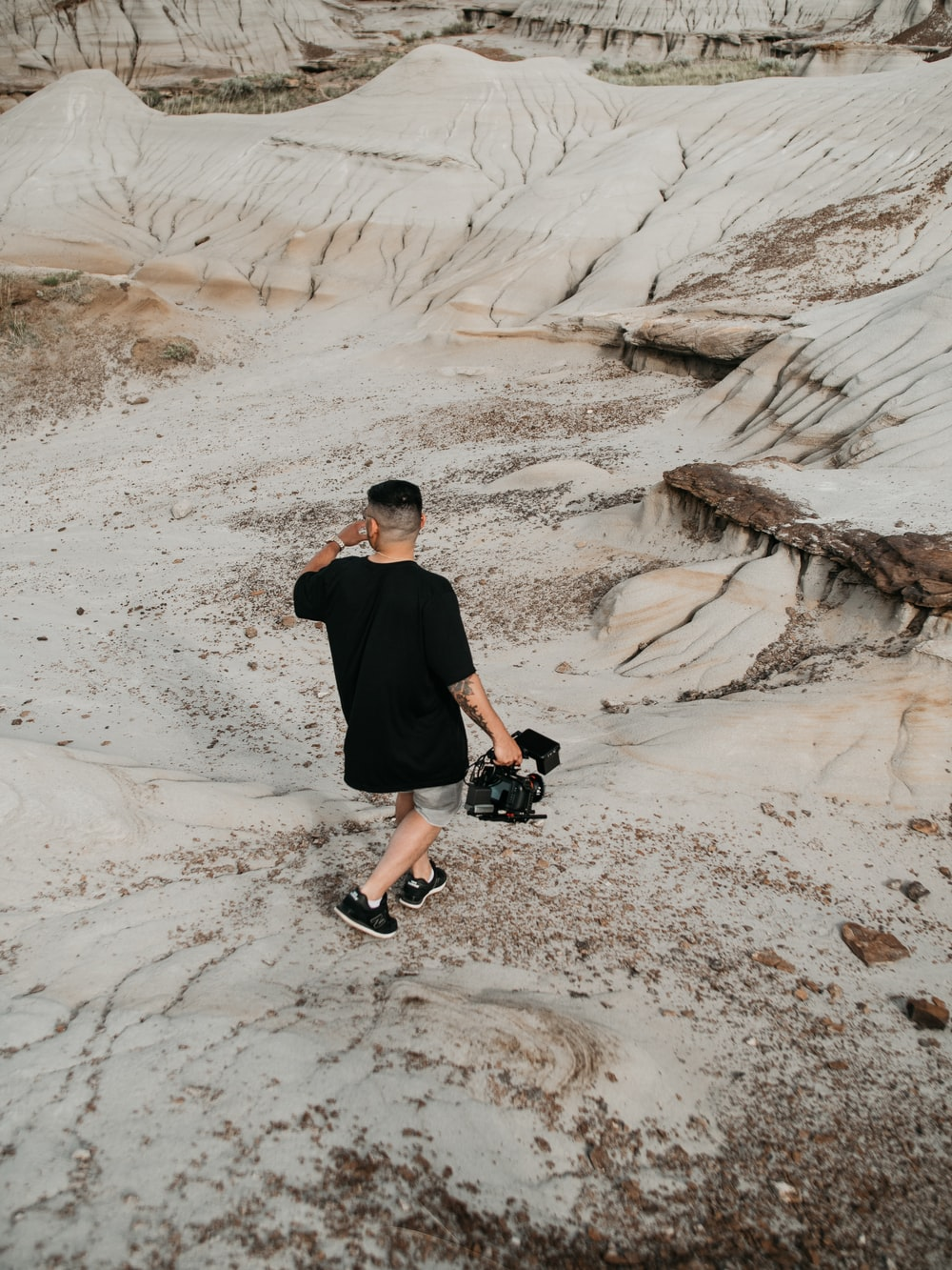 man in black t-shirt and black pants sitting on brown rock formation during daytime