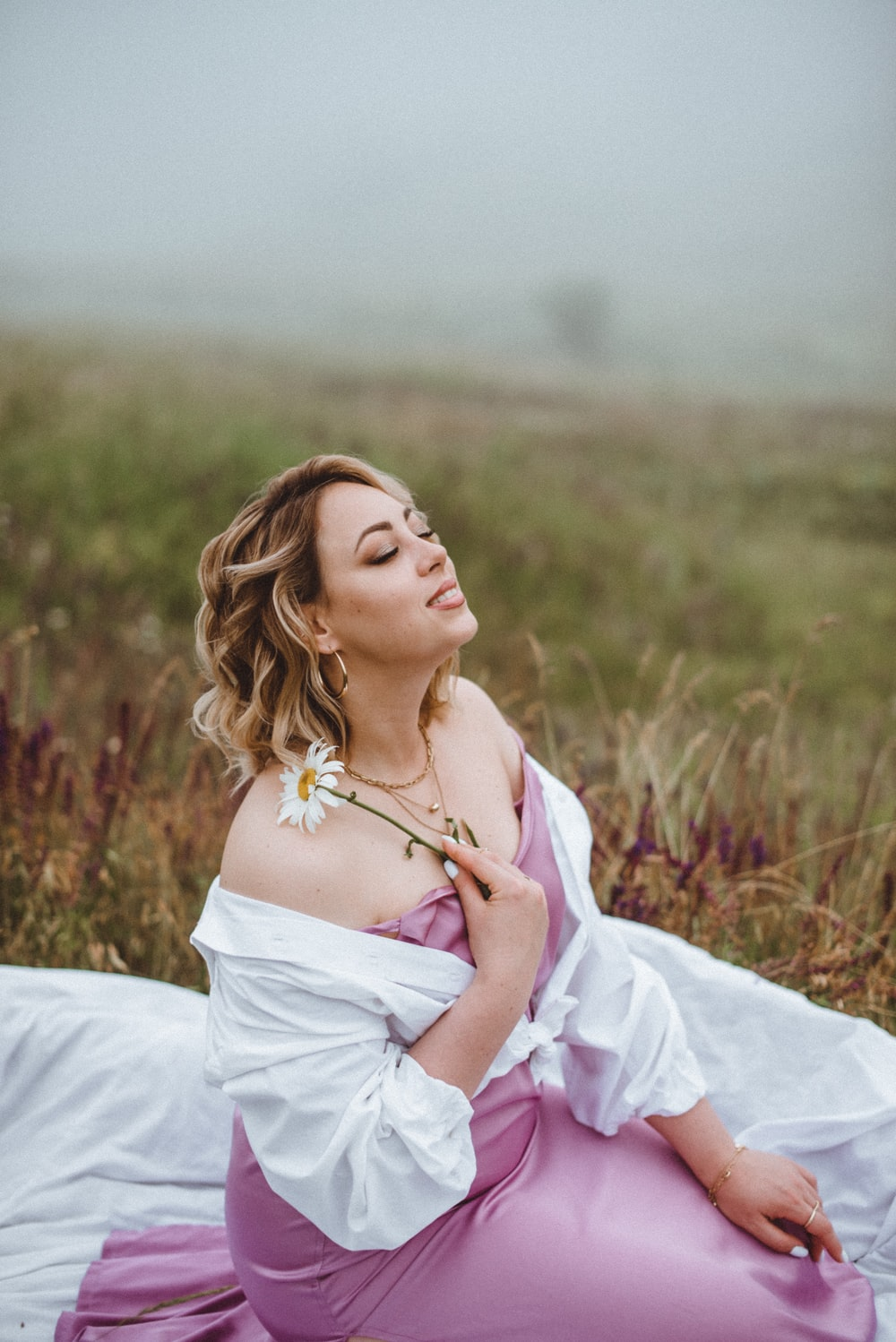 woman in white dress lying on grass field during daytime