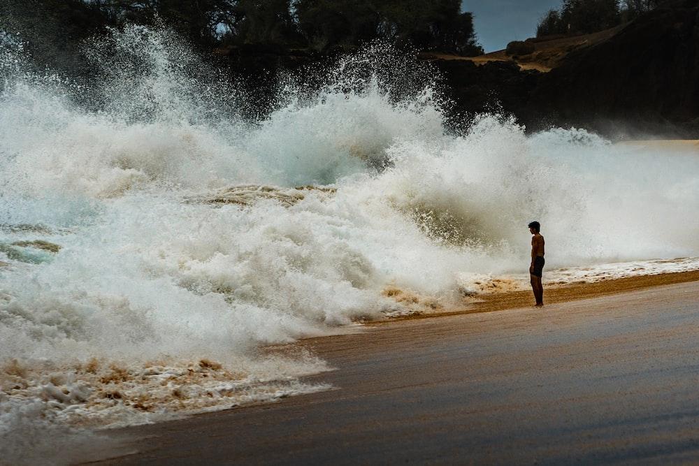 man in black shorts standing on seashore during daytime