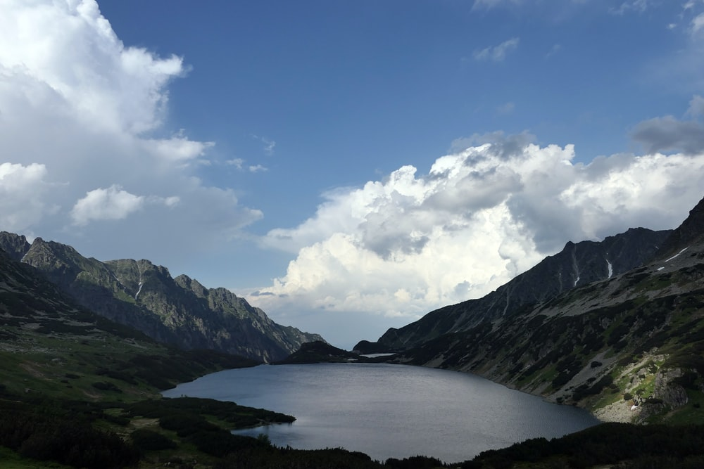 lake in the middle of mountains under blue sky and white clouds during daytime