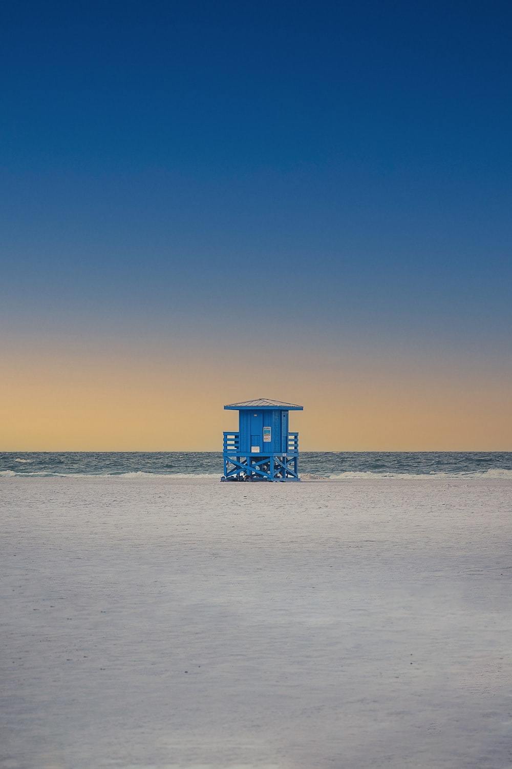 blue wooden lifeguard house on beach during daytime
