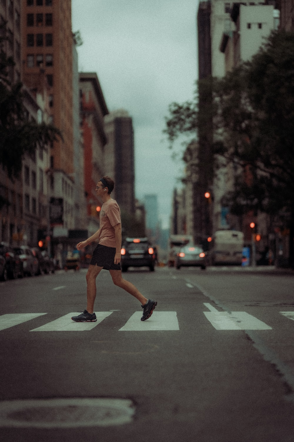 man in brown shirt and black shorts running on road during daytime