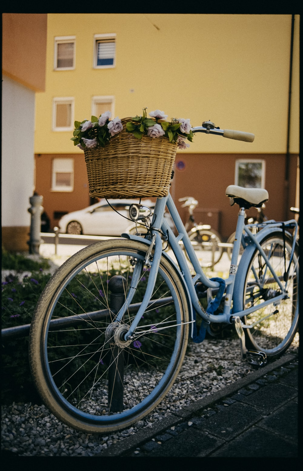 blue city bike with basket of flowers