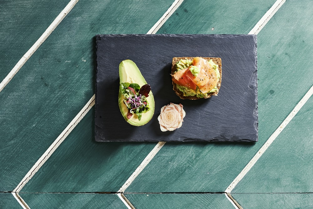 sliced avocado fruit on blue wooden chopping board